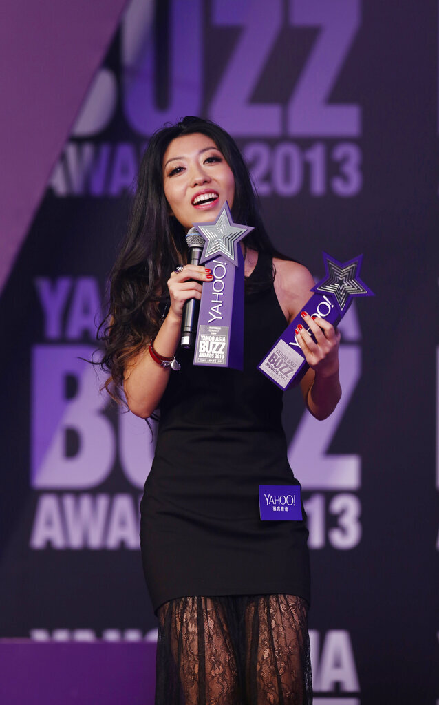 FILE - In this Dec. 1, 2013 file photo, Chinese singer-songwriter Wanting Qu holds two trophies after winning Hong Kong Most Popular Singer-Songwriter and the Best Mandarin Song at the Yahoo Buzz Awards in Hong Kong. A Chinese pop star whose mother had been held in custody since being arrested for corruption six years ago said that the charge had been removed by Chinese prosecutors. (AP Photo/Kin Cheung, File)