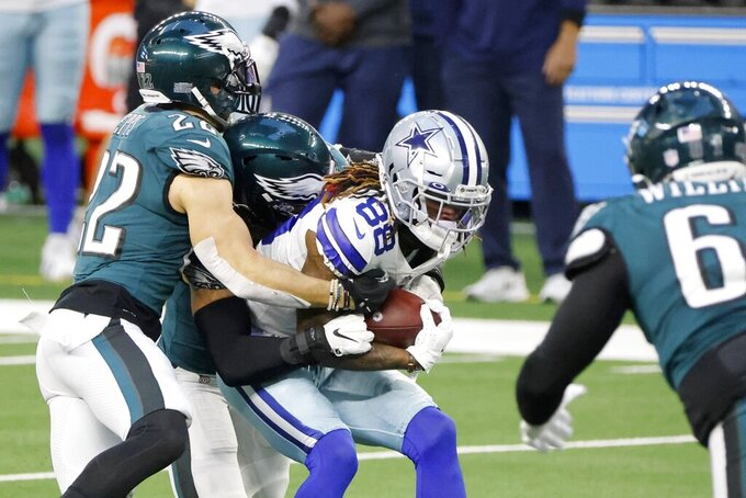 Dallas Cowboys wide receiver CeeDee Lamb (88) is tackled by Philadelphia Eagles safety Marcus Epps (22) and others after catching a pass for a first down in the first half of an NFL football game in Arlington, Texas, Sunday, Dec. 27. 2020. (AP Photo/Michael Ainsworth)