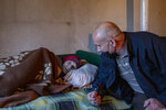 Kosovo Albanian Fadil Rama, right, speaks to a Kosovo Serb Blagica Dicic a lonely 92-year old woman in a remote village of Vaganesh, Kosovo on Thursday, Nov. 19, 2020. Blagica Dicic is in failing health, and is the only resident of a remote ethnic Serb minority village in the mountains of eastern Kosovo that's been abandoned by all its other inhabitants, even her own children, but Fadil Rama, 54, comes from the other side of Kosovo's bitter ethnic divide. (AP Photo/Visar Kryeziu)