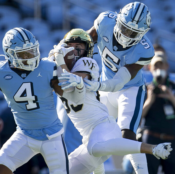 Wake Forest's Taylor Morin (83) manages to maintain control of a 28-yard pass reception from quarterback Sam Hartman (10) in the second quarter under defensive pressure from North Carolina's Patrice Rene (5) and Trey Morrison (4) at Kenan Stadium on Saturday, November 14, 2020 in Chapel Hill, N.C.(Robert Willett/The News & Observer via AP)
