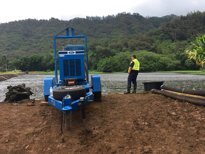 A fire official watches as water is pumped from a reservoir where a dam came close to overflowing in Honolulu on Thursday, Sept. 13, 2018. Honolulu officials say they may need to evacuate 10,000 people from a residential neighborhood if water in the reservoir continues to rise after heavy rains from a tropical storm. (AP Photo/Caleb Jones)