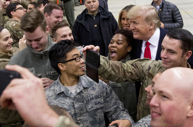 FILE - In this Thursday, Dec. 27, 2018 file photo, President Donald Trump, center right, and first lady Melania Trump, center left, greet members of the military at Ramstein Air Base, Germany. After more than a year of thinly veiled threats that the United States could start pulling troops out of Germany unless the country increases its defense spending to NATO standards, President Donald Trump appears to be going ahead with the hardball approach with a plan to reduce the American military presence in the country by more than 25 percent. (AP Photo/Andrew Harnik, file)
