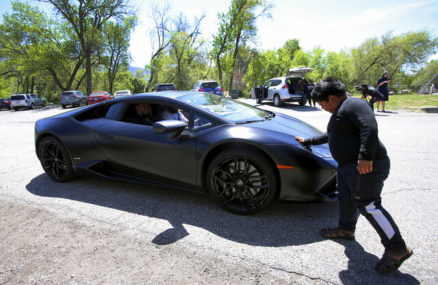Adrian Zamarripa touches the front of Jeremy Neves' Lamborghini Huracan in Ogden, Utah, Tuesday, May 5, 2020. Adrian, who tried to drive his parents' car to California Monday and was stopped by the Utah Highway Patrol, got a ride on the Lamborghini Tuesday from Neves who heard about the news and drove his car from another county for Adrian. (Scott G Winterton/The Deseret News via AP)