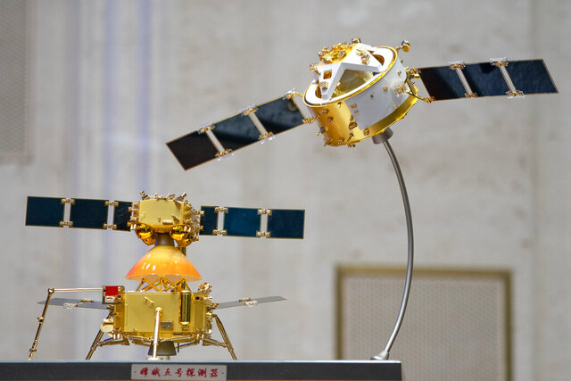 A model of China's Chang'e 5 lunar orbiter and lander are displayed before a press conference at the State Council Information Office in Beijing, Thursday, Dec. 17, 2020. Following the successful return of moon rocks by its Chang'e 5 robotic probe, China is preparing for future missions that could set the stage for an eventual  lunar base to host human explorers. (AP Photo/Mark Schiefelbein)