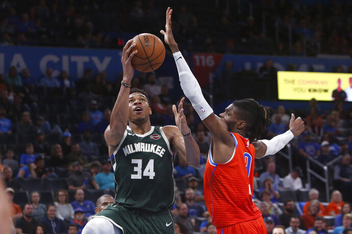 Milwaukee Bucks forward Giannis Antetokounmpo (34) goes to the basket in front of Oklahoma City Thunder forward Nerlens Noel (9) during the second half of an NBA basketball game Sunday, Nov. 10, 2019, in Oklahoma City. (AP Photo/Sue Ogrocki)
