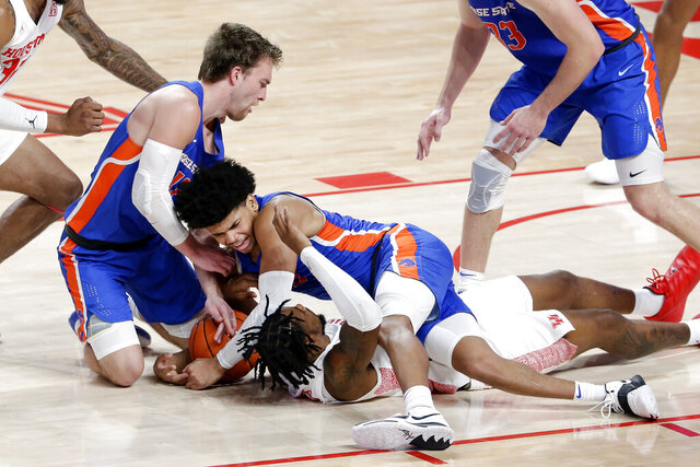 Boise State guard Max Rice, left, and guard RayJ Dennis, center, battle for the loose ball over Houston forward J'Wan Roberts, bottom, during the first half of an NCAA college basketball game Friday, Nov. 27, 2020, in Houston. (AP Photo/Michael Wyke)