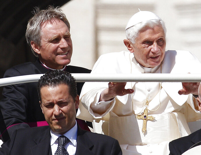 FILE - In this file photo taken on Wednesday, May 2, 2012, Pope Benedict XVI, right, arrives in St. Peter's square at the Vatican for a general audience as his then-butler Paolo Gabriele, bottom, and his personal secretary Georg Gaenswein sit in the car with him. Paolo Gabriele, the Vatican butler who was convicted of stealing and leaking Pope Benedict XVI's private papers in 2012, has died at age 54, the Vatican said. Vatican News, the Holy See's media agency, said Gabriele died Tuesday after a long illness. (AP Photo/Alessandra Tarantino, File)