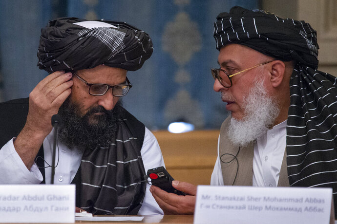 "FILE - In this May 28, 2019, file photo, Mullah Abdul Ghani Baradar, the Taliban group's top political leader, left, and Sher Mohammad Abbas Stanikzai, the Taliban's chief negotiator, talk to each other during a meeting in Moscow, Russia. Taliban officials say several of the group's members have been freed from Afghan jails, including former shadow governors, the first move of its kind since a peace deal that seemed imminent was declared ""dead"" and just days after a U.S. envoy met with Mullah Abdul Ghani Baradar and other top Taliban leaders in the Pakistani capital of Islamabad. (AP Photo/Alexander Zemlianichenko, File)"
