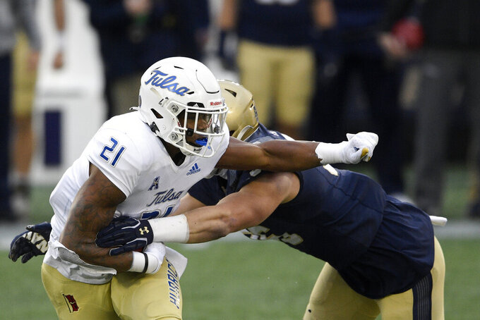 Tulsa running back T.K. Wilkerson (21) runs with the ball against Navy defensive tackle Jackson Perkins, right, during the first half of an NCAA college football game, Saturday, Dec. 5, 2020, in Annapolis, Md. (AP Photo/Nick Wass)