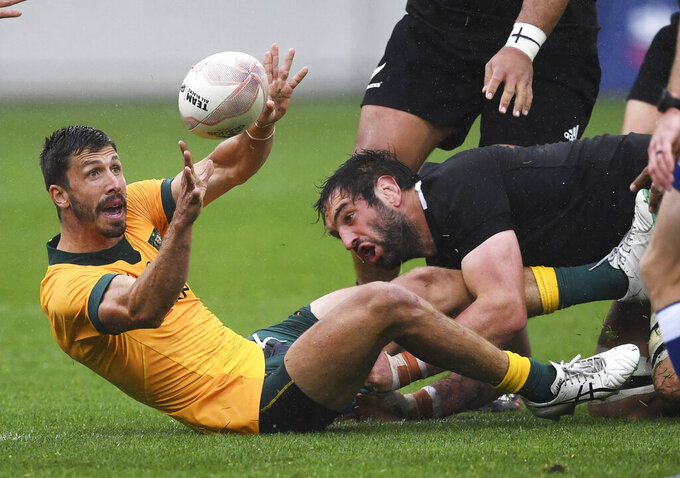 Australia's Jake Gordon passes the ball in the tackle of New Zealand's Sam Whitelock during the Bledisloe Cup rugby game between the All Blacks and the Wallabies in Wellington, New Zealand, Sunday, Oct.11, 2020. (Andrew Cornaga/Photosport via AP)