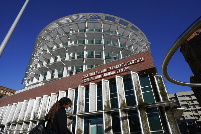 A woman wearing a mask walks under a sign for Zuckerberg San Francisco General Hospital and Trauma Center in San Francisco, Monday, Dec. 14, 2020. Supervisors in San Francisco will vote on a nonbinding and symbolic resolution to condemn the naming of the city's public general hospital for Facebook CEO Mark Zuckerberg in 2015 after he and his wife, Dr. Priscilla Chan, donated $75 million for a new trauma center. Supporters of a condemnation say the Facebook co-founder and CEO has endangered public health and threatened democracy with a platform that spreads misinformation and invaded people's privacy. (AP Photo/Jeff Chiu)