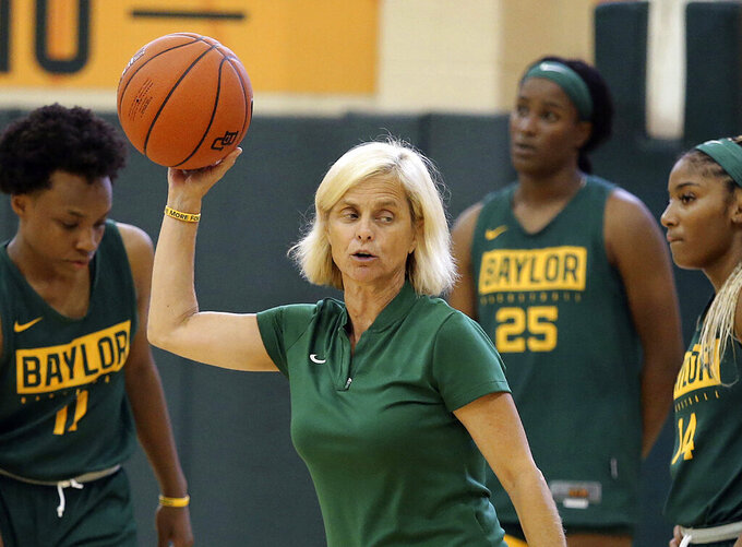 FILE - In this Sept. 30, 2019, file photo, Baylor women's coach Kim Mulkey, center, talks with players during the NCAA college basketball team's practice in Waco, Texas. The NCAA Division I Council on Wednesday, June 17, 2020, approved a plan to allow college basketball players to start working with their coaches for the first time since the pandemic wiped out March Madness. The summer access period for men's and women's players will begin July 20. (Jerry Larson/Waco Tribune-Herald via AP, File)