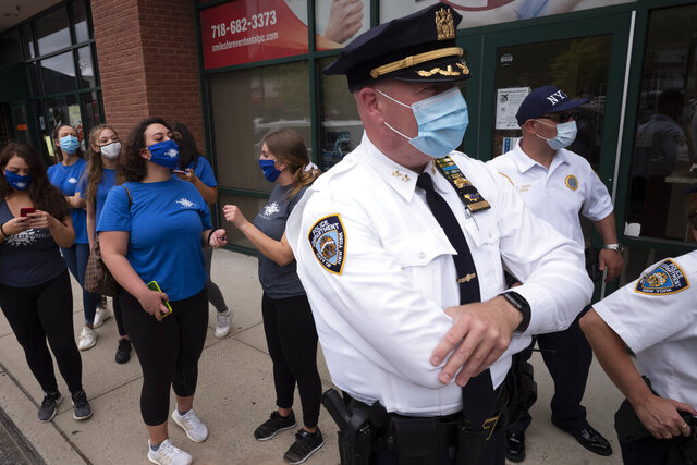 Tanning salon workers, left, stand behind police outside the Staten Island business, Thursday, May 28, 2020, in New York. Owner Bobby Catone opened the salon briefly Thursday morning in defiance of a law requiring non-essential businesses to remain closed during the coronavirus pandemic. (AP Photo/Mark Lennihan)