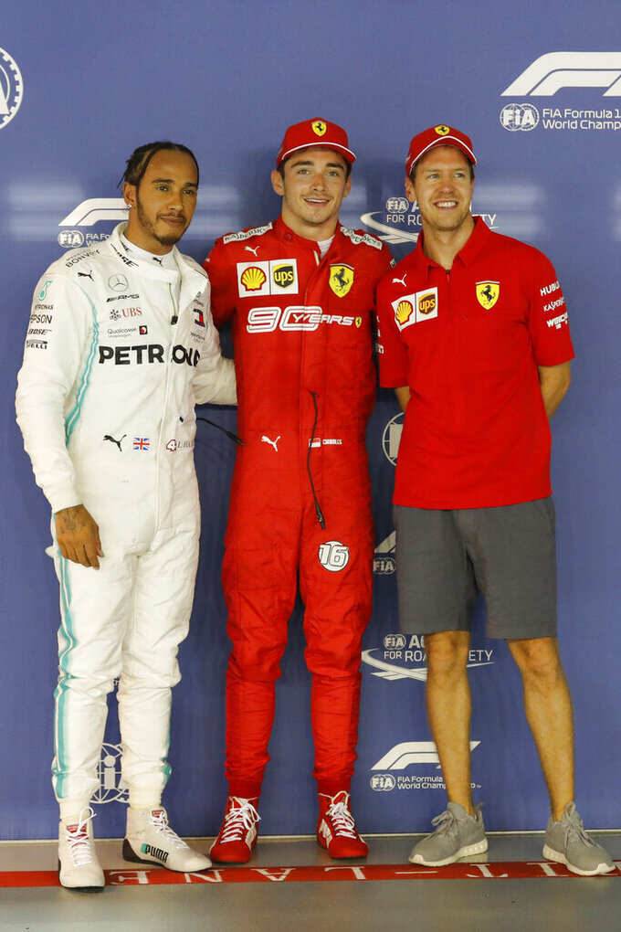 Ferrari driver Charles Leclerc of Monaco, center, poses with his teammate Sebastian Vettel of Germany, right, and Mercedes driver Lewis Hamilton of Britain after taking pole in the qualifying session for the Singapore Formula One Grand Prix at the Marina Bay City Circuit in Singapore, Saturday, Sept. 21, 2019. Hamilton finished second as Vettel was third. (AP Photo/Vincent Thian)