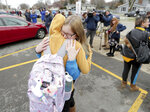Alexis Grady, facing, a 17-year-old senior, hugs her friend Arissa Goodman outside Waukesha South High School in Waukesha, Wis., on Monday, Dec. 2, 2019. Gunshots were exchanged between a student and a school resource officer inside Waukesha South High School, according to school officials. (Mike De Sisti/Milwaukee Journal-Sentinel via AP)