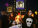 Brittany Canfield, left, holds a photo of her grandmother, Angelita Lara, while Steven Rodriguez holds a photo of Debby Jean Stephens at the All Souls Procession in Tucson, Ariz., on Nov. 4, 2018. Dozens of Tucson events have already been canceled, like the street fairs, postponed, like the El Tour De Tucson, or moved online, like the All Souls Procession or the Tucson Festival of Books, as organizers, government officials, and attendees shy away from gatherings that could contribute to the spread of the coronavirus. (Rick Wiley/Arizona Daily Star via AP)