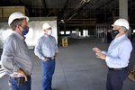 Republicans U.S. Sen. Steve Daines, left, and Rep. Greg Gianforte listen to a representative of FLIR Systems describe the technology company's new facility under construction on Wednesday, Sept. 2, 2020 in Bozeman, Mont. After working together in the corporate world the two Republicans are on the cusp of solidifying their influence over Montana politics for years to come. (AP Photo/Matthew Brown)