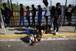 Carlos Ernesto Gutierrez, a migrant from El Salvador, changes his shoes on the bridge spanning the Suchiate River, in Tecun Uman, on the border with Mexico, Tuesday, Jan. 21, 2020, as he waits with a small group of migrants from El Salvador at this legal port of entry. (AP Photo/Moises Castillo)