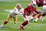 Arizona Cardinals quarterback Kyler Murray (1) eludes the reach of San Francisco 49ers defensive end Kerry Hyder (92) during the first half of an NFL football game, Saturday, Dec. 26, 2020, in Glendale, Ariz. (AP Photo/Ross D. Franklin)