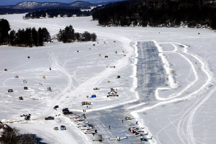 FILE - In this Feb. 28, 2015, file photo, planes are parked after landing on a frozen Lake Winnipesaukee in Alton, N.H. The ice runway will remain closed this winter because mild weather, which has made the ice unsafe to support maintenance vehicles and aircraft, according to an official. (AP Photo/Jim Cole, File)