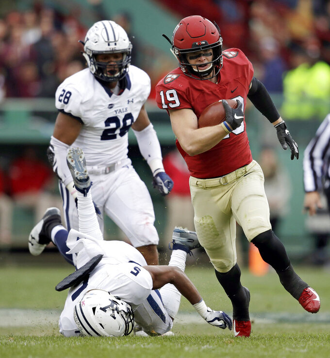Harvard wide receiver Tyler Adams (19) breaks free as Yale defensive back Miles Oldacre, left, face plants into the turf on a touchdown run during the first half of an NCAA college football game at Fenway Park in Boston, Saturday, Nov. 17, 2018. At rear is Yale defensive end Christian Sampleton (28). (AP Photo/Charles Krupa)