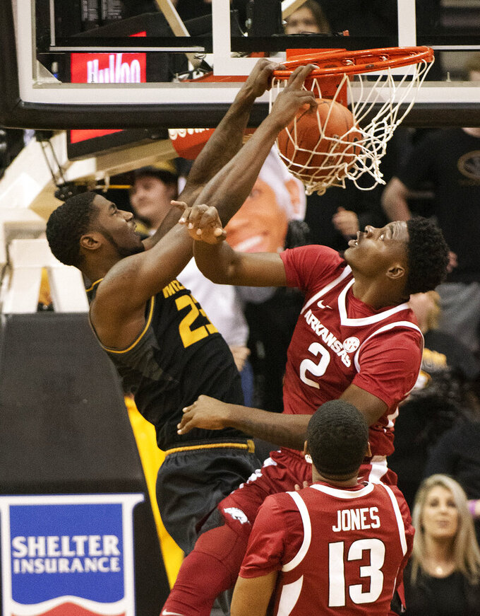 Missouri's Jeremiah Tilmon, left, dunks over Arkansas's Adrio Bailey, right, during the first half of an NCAA college basketball game Tuesday, Feb. 12, 2019, in Columbia, Mo. (AP Photo/L.G. Patterson)