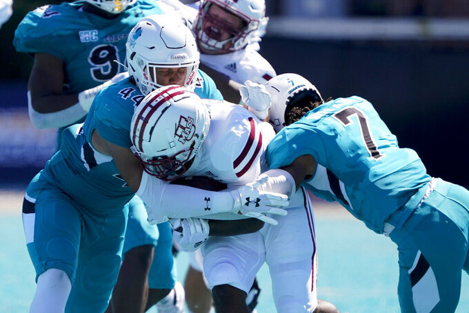 Massachusetts running back Kay'Ron Adams is tackled by Coastal Carolina linebacker E.J. Porter, left, and cornerback Lance Boykin during the first half of an NCAA college football game on Saturday, Sept. 25, 2021, in Conway, S.C. (AP Photo/Chris Carlson)