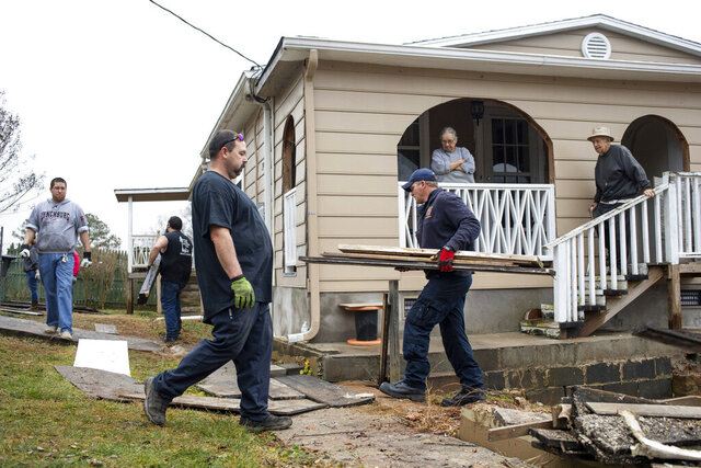 In a Saturday, Jan. 4, 2020 photo, left to right, nurse Sean McGannon from the CMG Stroobants Cardiovascular Center, volunteer Daron Moon, Roger Woody from the Monelison Fire Department, Capt. Thomas Bartell from Amherst Public Safety, remove debris from the front yard of local Amherst residents Maria and Angel Alberio during a community outreach event in Amherst, Va. (Emily Elconin/The News & Advance via AP)/The News & Advance via AP