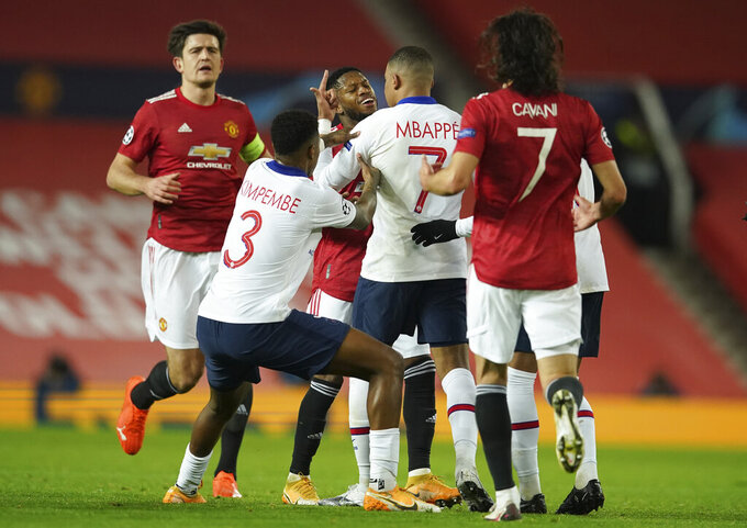 Manchester United's Fred, centre is confronted by PSG players after an incident off the ball during a Group H Champions League soccer match between Manchester United and Paris Saint Germain at the Old Trafford stadium in Manchester, England, Wednesday, Dec. 2, 2020. (AP Photo/Dave Thompson)