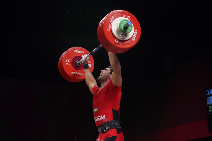 Akbar Djuraev of Uzbekistan completes his final lift, to set a new Olympic record, in the men's 109kg weightlifting event at the 2020 Summer Olympics, Tuesday, Aug. 3, 2021, in Tokyo, Japan. (AP Photo/Seth Wenig)