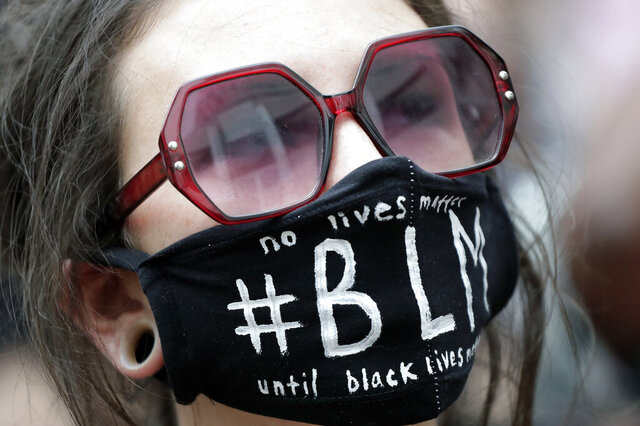 A demonstrator listens to speakers during a protest at Orlando City Hall Tuesday, June 2, 2020, in Orlando, Fla., over the death of George Floyd. Floyd died after being restrained by Minneapolis police officers on May 25. (AP Photo/John Raoux)