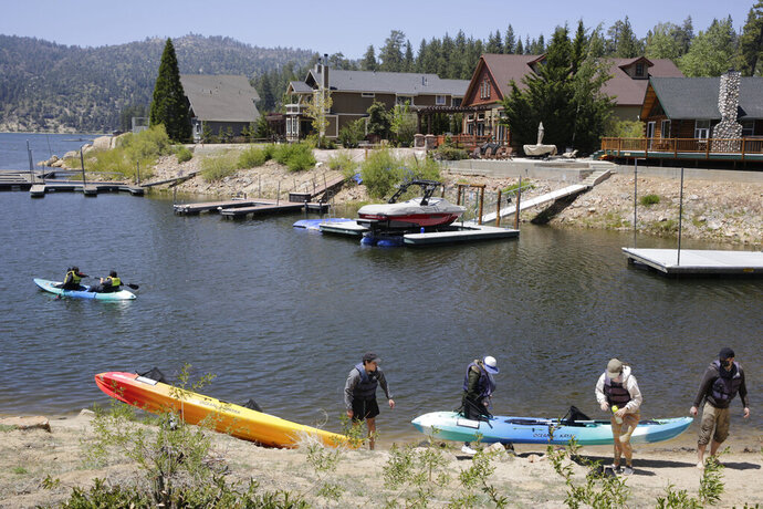 Tourists enjoy the outdoors in Big Bear, Calif, Friday, May 22, 2020. The mountain destination of Big Bear Lake announced officials would not enforce the governor's orders, arguing it has kept COVID-19 cases manageable while the economy has suffered. (AP Photo/Damian Dovarganes)