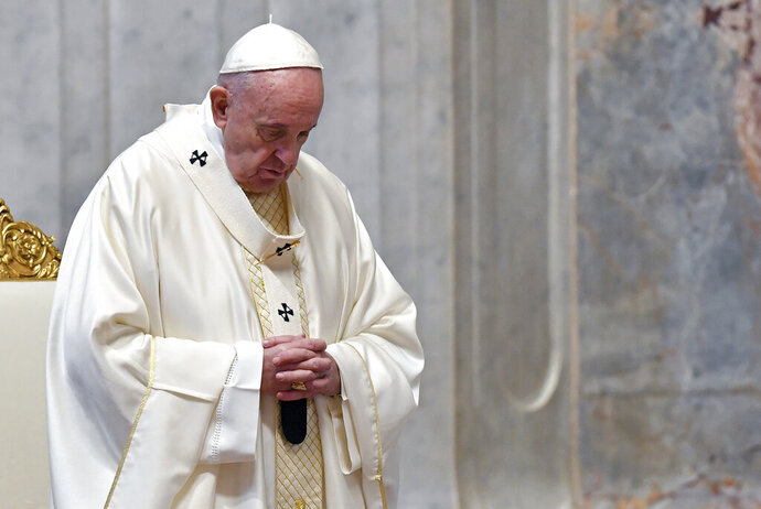 Pope Francis attends a Mass for Holy Thursday, inside St. Peter's Basilica at the Vatican, Thursday, April 9, 2020. Francis celebrated the Holy Week Mass in St. Peter's Basilica, which was largely empty of faithful because of restrictions aimed at containing the spread of COVID-19. The new coronavirus causes mild or moderate symptoms for most people, but for some, especially older adults and people with existing health problems, it can cause more severe illness or death.  (Alessandro Di Meo/Pool Photo via AP)