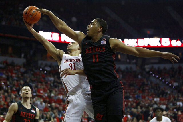 San Diego State's Matt Mitchell (11) goes for the block against UNLV's Marvin Coleman (31) during the first half of an NCAA college basketball game on Sunday, Dec. 26, 2020, in Las Vegas. (AP Photo/Joe Buglewicz)