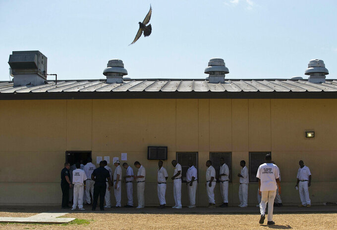 FILE - In this June 18, 2015, file photo, prisoners stand in a crowded lunch line during a prison tour at Elmore Correctional Facility in Elmore, Ala.  Alabama lawmakers see the possibility of a special session on prison construction this summer as Gov. Kay Ivey's plan to rent prisons from private companies has been hit by setbacks.  The lease plan faces a June 1, 2021 deadline for the companies to secure financing, after which the state or the companies can back out of the deal.Alabama lawmakers see the possibility of a special session on prison construction this summer as Ivey's plan to rent prisons from private companies has been hit by setbacks.  (AP Photo/Brynn Anderson, File)