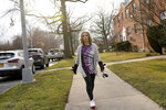 Catherine Busa takes a walk around her neighborhood as part of her recovery from COVID-19 in New York, Wednesday, Jan. 13, 2021. The 54-year-old New York City school secretary didn't have any underlying health problems when she caught the coronavirus in March and recovered at her Queens home. But some symptoms lingered. After eights months of suffering, she made her way to Jamaica Hospital Medical Center — to a clinic specifically for post-COVID-19 care. (AP Photo/Seth Wenig)