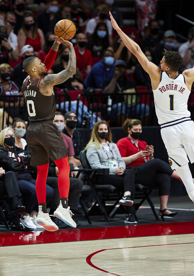 Portland Trail Blazers guard Damian Lillard shoots a 3-point basket over Denver Nuggets forward Michael Porter Jr. during the first half of Game 6 of an NBA basketball first-round playoff series Thursday, June 3, 2021, in Portland, Ore. (AP Photo/Craig Mitchelldyer)