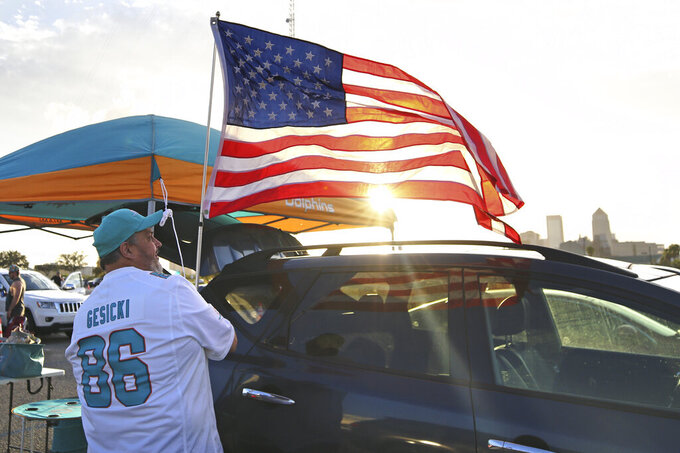 Terry Mohr of Brooklyn, N.Y. hoists a flag as he tailgates with friends before an NFL football game between the Jacksonville Jaguars and the Miami Dolphins, Thursday, Sept. 24, 2020, in Jacksonville, Fla. (AP Photo/Stephen B. Morton)
