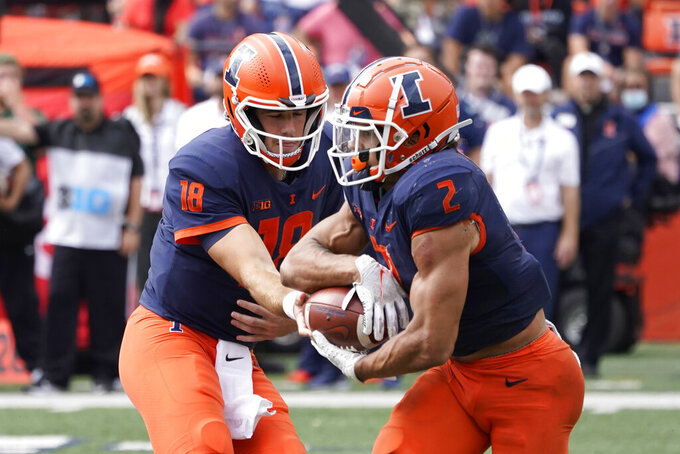 Illinois quarterback Brandon Peters (18) hands the ball off to Illinois running back Chase Brown for an 80-yard touchdown run during the second half of an NCAA college football game against Charlotte Saturday, Oct. 2, 2021, in Champaign, Ill. Illinois won 24-14. (AP Photo/Charles Rex Arbogast)