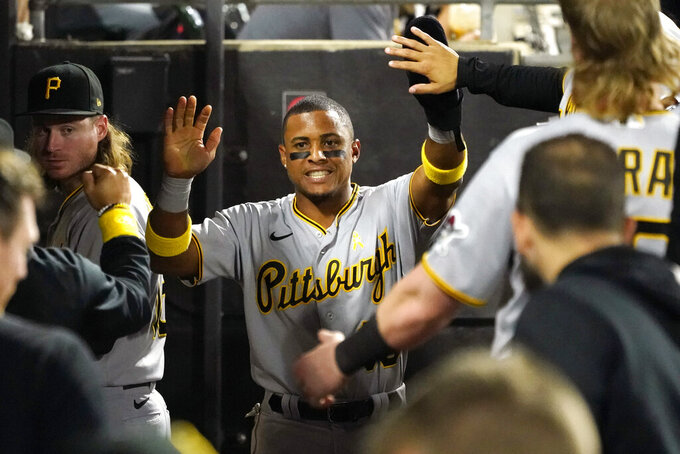 Pittsburgh Pirates' Wilmer Difo is greeted in the dugout after scoring on a single by Cole Tucker during the fifth inning of a baseball game against the Chicago White Sox Wednesday, Sept. 1, 2021, in Chicago. (AP Photo/Charles Rex Arbogast)