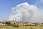 A plume of smoke rises from the Richard Spring wildfire on Wednesday, Aug. 11, 2021, north of Lame Deer, Mont. The fire spread quickly Wednesday as strong winds pushed the flames across rough, forested terrain. (AP photo/Matthew Brown)