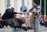 In this Thursday, June 18, 2020, photo, members of an impromptu audience thank musician Mark Kraszewski, right, who collects tips as he greets fans who stopped at Brooklyn's Prospect Park boathouse to listen to him perform with Alegba and Friends in one of the group's nightly free concerts in New York. Kraszewski, who normally plays in bars and restaurants, said,