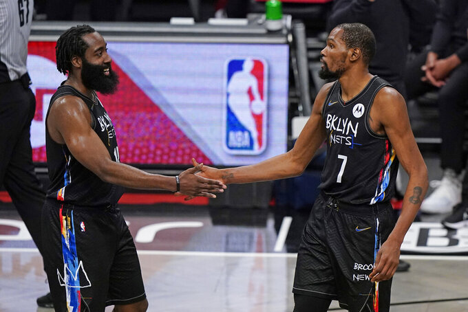 Brooklyn Nets forward Kevin Durant (7) congratulates Brooklyn Nets guard James Harden (13) during the final seconds of the fourth quarter of an NBA basketball game against the Los Angeles Clippers, Tuesday, Feb. 2, 2021, in New York. The Nets defeated the Clippers 124-120. (AP Photo/Kathy Willens)