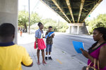 In June 4, 2016 photo provided by Deep Center, Deep Center artists observe how people interact with the space around and under the I-16 overpass in Savannah, Ga. Deep Center works with young writers to share their stories with policy makers, judges, politicians, police officers and the like.(Linneah Anders/Deep Center via AP)