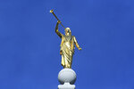 FILE - In this April 6, 2019, file photo, the angel Moroni statue sits atop the Salt Lake City temple, in Salt Lake City. The Church of Jesus Christ of Latter-day Saints came out Monday, May 13, 2019, against a comprehensive nondiscrimination bill that faces long odds in Congress, saying the legislation doesn't