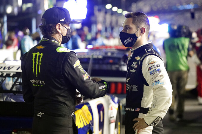 Kurt Busch, left, and Kaz Grala, talk on pit road before the second of two qualifying NASCAR auto races for the Daytona 500 at Daytona International Speedway, Thursday, Feb. 11, 2021, in Daytona Beach, Fla. (AP Photo/John Raoux)
