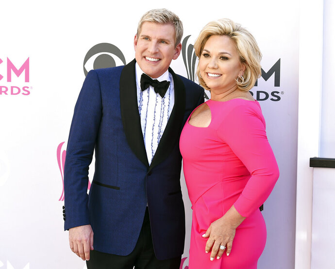 FILE - This April 2, 2017 file photo shows Todd Chrisley, left, and his wife Julie Chrisley at the 52nd annual Academy of Country Music Awards in Las Vegas. The couple are accusing a Georgia tax official of abusing his office to pursue