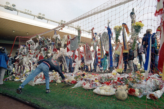 FiLE - In this file photo dated April 16, 1989, a Liverpool Football Club fan places a pair of football boots in the goal at the Kop end of Anfield Stadium as hundreds came to mourn the loss of fellow Liverpool fans.  Liverpool players and staff have observed 97 seconds of silence in honor of Andrew Devine. The lifelong fan died Tuesday, July 27, 2021 from long-term injuries sustained in the Hillsborough disaster. He was 55.  (AP Photo/Peter Kemp, File)