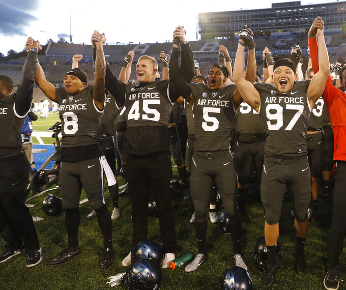 From left, Air Force wide receiver Marcus Bennett. linebacker R.J. Jackson, quarterback Donald Hammond III and defensive lineman Kaleb Nunez sing the school song with teammates after an NCAA college football game against Colorado State Thursday, Nov. 22, 2018, at Air Force Academy, Colo. Air Force won 27-19. (AP Photo/David Zalubowski)