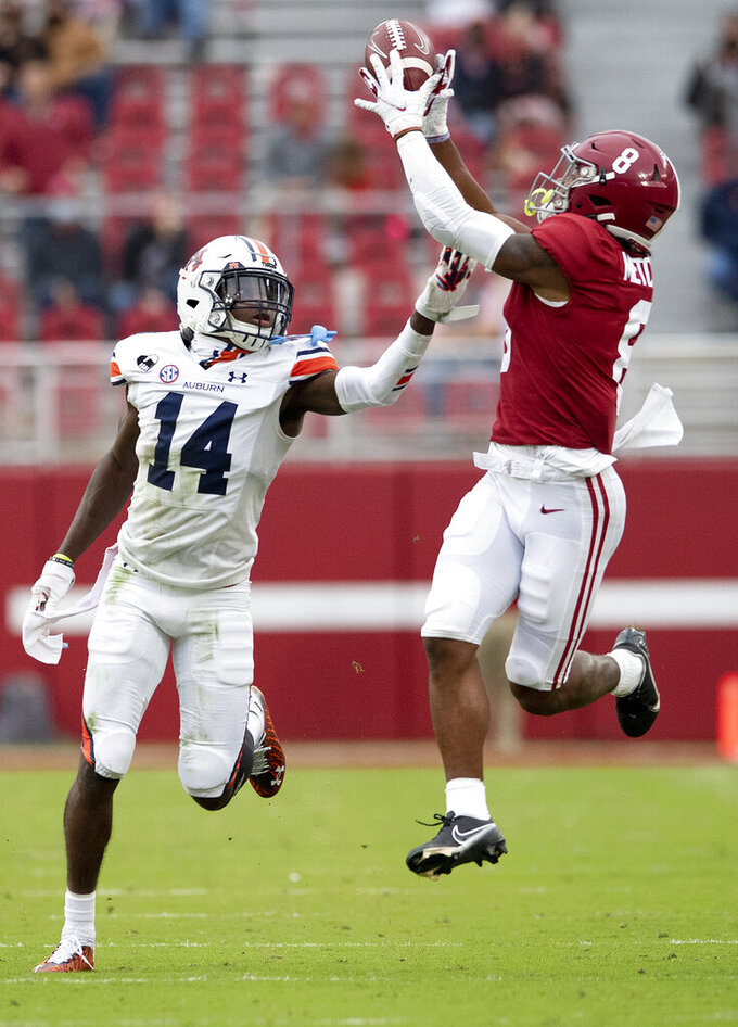 Auburn defensive back Nehemiah Pritchett (14) defends on an incomplete pass to Alabama wide receiver John Metchie III (8) during an NCAA college football game Saturday, Nov. 28, 2020, in Tuscaloosa, Ala. (Mickey Welsh/The Montgomery Advertiser via AP)